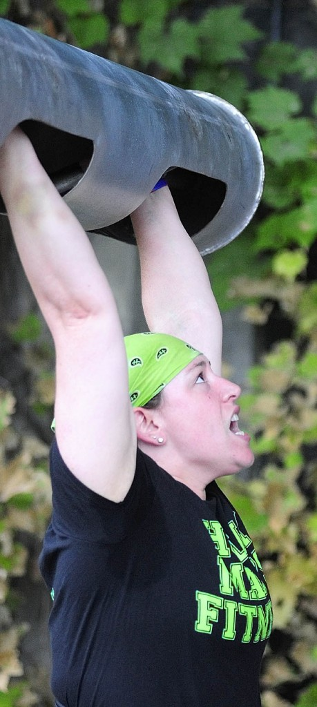 HOIST: Andrea Shorey, of Clinton, strains to lift the bar overhead in the log clean and press event during the Downtown Throwdown strongman contest on Front Street Saturday morning in downtown Augusta.