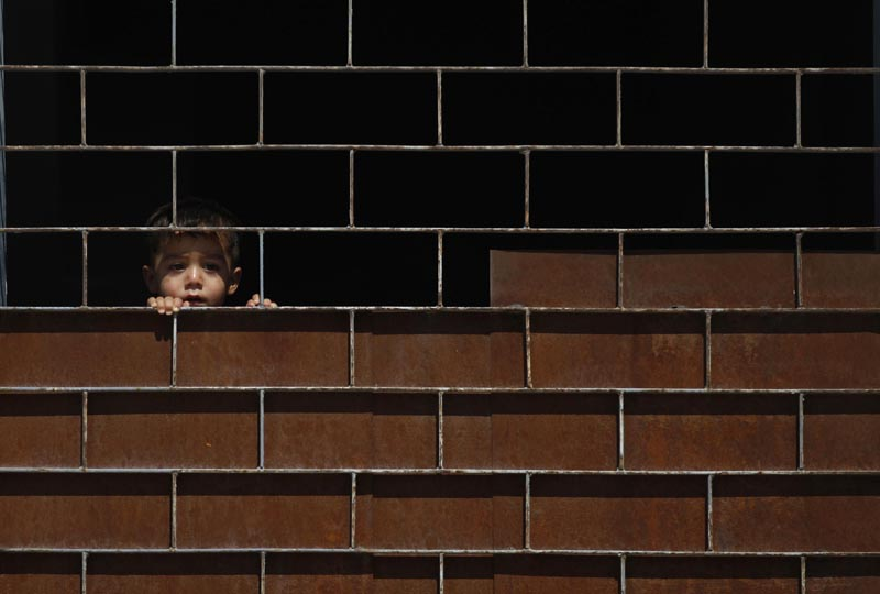 A Syrian boy watches on Tuesday as his friends play at a school where they live after they have fled their homes due to fighting, in the town of Kafr Hamra, Syria.
