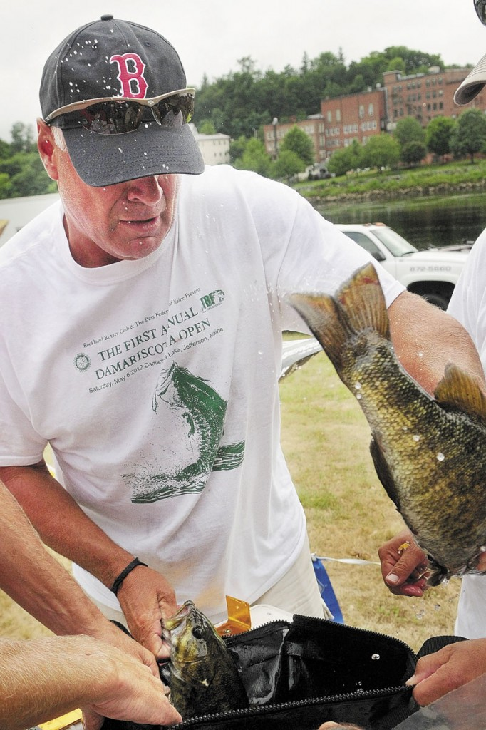 Dave Austin, of Augusta, loads fish into a bag to be weighed at the end of the Augusta Fest bass fishing tournament on Saturday at the East Side Boat Landing. Austin and his partner, Chris Brewer, of Livermore, beat seven other teams with a total of 11.03 pounds for their seven fish entered. Most Augusta Fest events, except for this and the strongman-style contest held earlier in the morning, were canceled because of the weather.