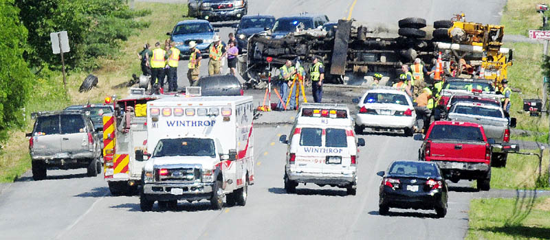Police officers and firefighters work at the scene of a serious motor vehicle accident this afternoon on U.S. Route 202 near the East Winthrop Post Office.