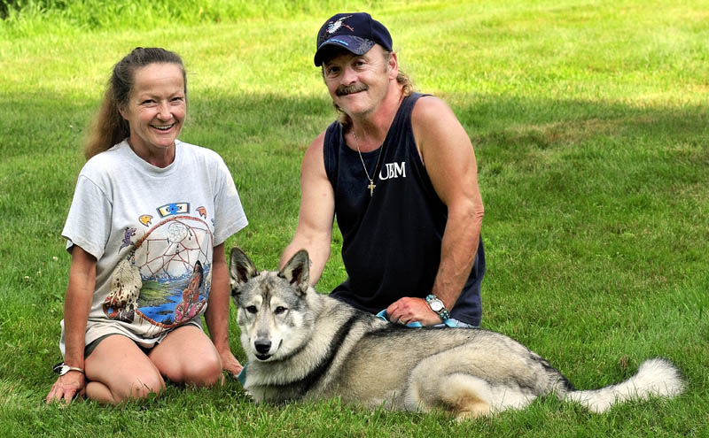 FAMILY: Julie and Gene Mitchell of Detroit with their two-year-old wolf hybrid named Wolf.