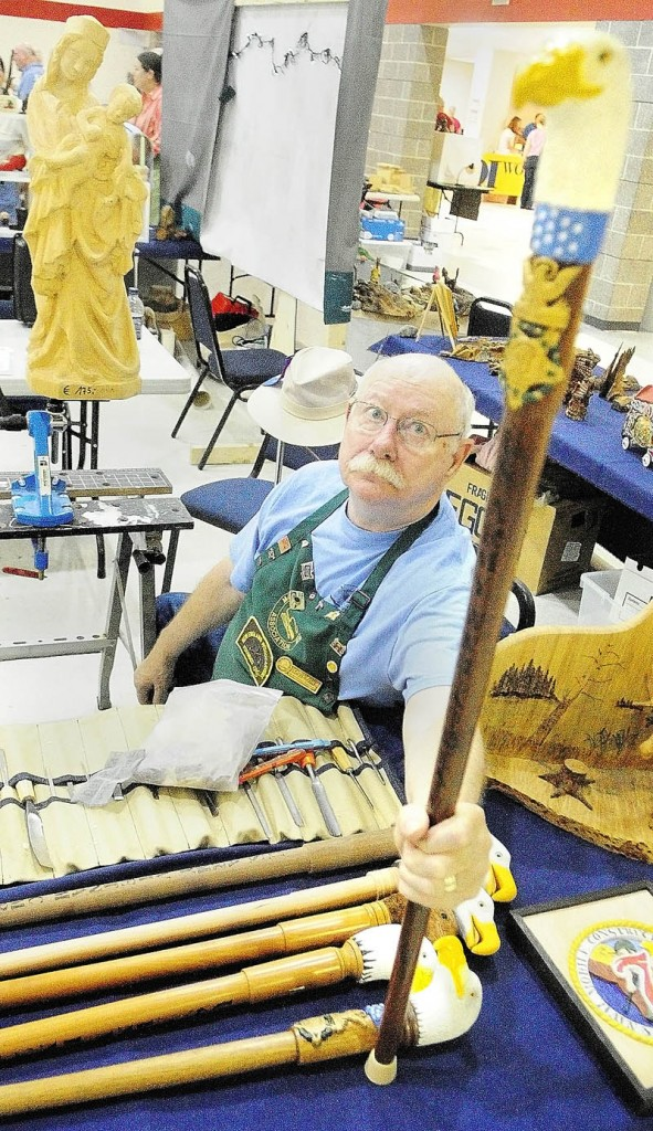 Chuck Friis, president of the Poland Springs chapter of the Maine Wood Carvers Association, talks about the eagle cane project at the Downeast Woodcarving & Wildlife Art Show at the Augusta Armory.