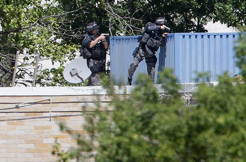 Armed police investigate the Sikh temple in Oak Creek, Wis., where a shooting took place on Sunday.