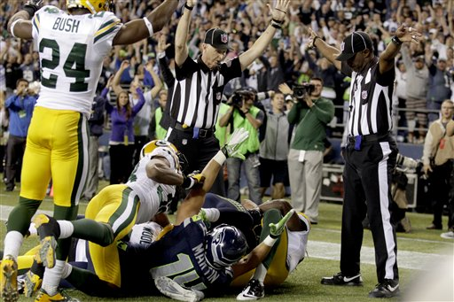 Officials signal a touchdown by Seattle Seahawks wide receiver Golden Tate, obscured, on the last play of an NFL football game against the Green Bay Packers, Monday, Sept. 24, 2012, in Seattle. The Seahawks won 14-12. (AP Photo/Stephen Brashear) NFLACTION12;