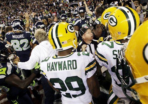 Officials try to sort out the final play of an NFL football game between the Green Bay Packers and the Seattle Seahawks as players and coaches swarm the field, Monday, Sept. 24, 2012, in Seattle. After a period of confusion, a Seahawks touchdown by wide receiver Golden Tate was allowed to stand for a 14-12 win. (AP Photo/Ted S. Warren) NFLACTION12;