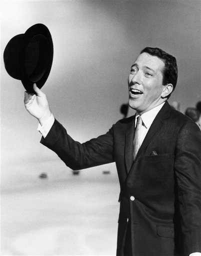 """FILE - In a May 12, 1961 file photo, Andy Williams performs a song on a television show. Emmy-winning TV host and """"Moon River"""" crooner Williams died Tuesday night, Sept, 25, 2012 at his home in Branson, Mo., following a year-long battle with bladder cancer. He was 84. (AP Photo, File) Singing Singer Holding Hat Looking Away Performance Standing"""