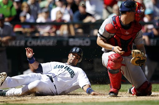 Seattle Mariners' Franklin Gutierrez, left, scores ahead of a tag by Boston Red Sox catcher Ryan Lavarnway in the fourth inning of a baseball game, Monday, Sept. 3, 2012, in Seattle. (AP Photo/Elaine Thompson) Safeco Field