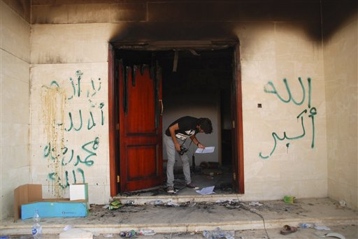 "A man looks at documents at the U.S. consulate in Benghazi, Libya, on Wednesday after an attack that killed four Americans, including Ambassador Chris Stevens. The graffiti reads, ""no God but God,"" ""God is great,"" and ""Muhammad is the Prophet."""