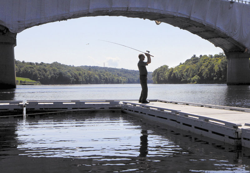 """A NICE CAST: Pat Merrill of Lewiston fishes for smallmouth bass on the Kennebec River in Augusta at the East Side Boat Landing Park on Friday. Moments earlier Merrill said he caught a nice 14-inch small bass. """"The fish are starting to bite again. The water is starting to cool down a bit,"""" said Merrill."""