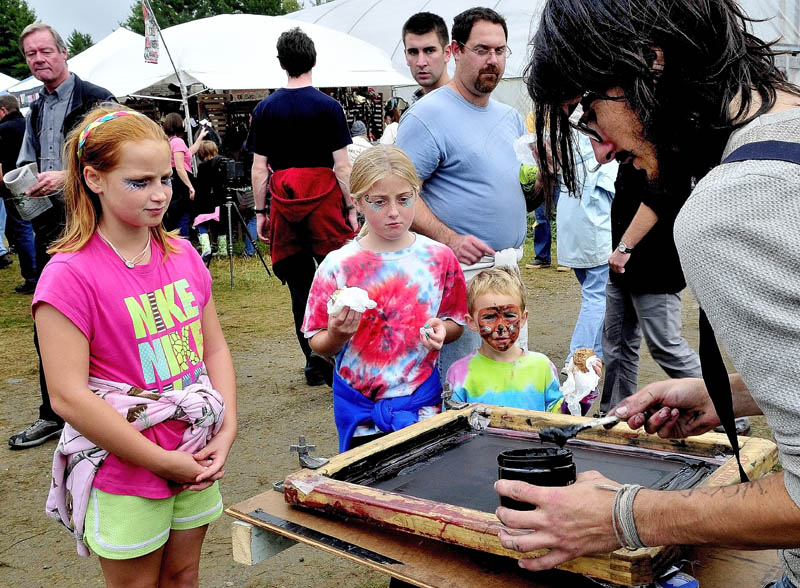 CONTRAST: Payrn Oak demonstrates black and white silk screen printing as a colorful trio of kids watch at the Common Ground Country Fair in Unity on Saturday. From left are Bella Russo, Shauna Hancock and Nico Russo.