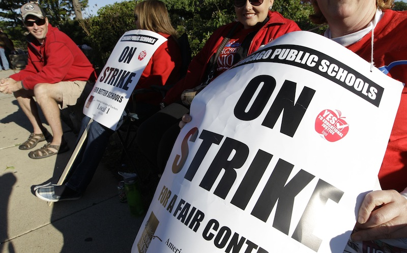Teachers picket outside Morgan Park High School in Chicago, Tuesday, Sept. 18, 2012, as a strike by the Chicago Teachers Union continues into its second week. CTU members in the nation's third-largest city will pore over the details of a contract settlement Tuesday as the clock ticks down to an afternoon meeting in which they are expected to vote on ending a seven-day strike that has kept 350,000 students out of class. (AP Photo/M. Spencer Green)