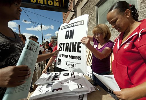 Members of the Chicago Teachers Union distribute strike signs at the union's strike headquarters in Chicago on Saturday. The union announced Sunday night that its 25,000 members will go on strike Monday morning for the first time in 25 years after contract talks with the school district failed. Chicago;USA