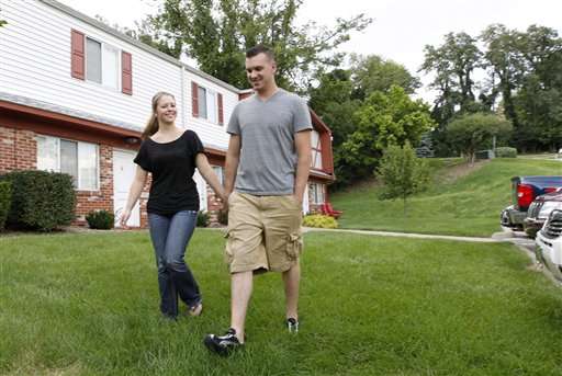 """Marine Sgt. Ron Strang, right, walks with his girlfriend, Monica Michna, in the yard by his home in Jefferson Hills, Pa., just south of Pittsburgh. The 28-year-old former Marine sergeant from Pittsburgh lost half of his left thigh muscle to shrapnel. Now, after an experimental cell treatment at the University of Pittsburgh Medical Center, """"I'm able to run a little bit"""" and play a light football game with friends, he said."""