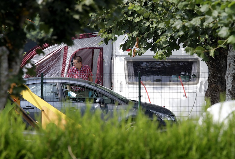 An investigator enters the trailer where the slain British family were holidaying in a camp site of Saint Jorioz, near Annecy, France Thursday, Sept. 6, 2012. A 4-year-old British girl hid for eight hours beneath the bodies of slain family members in the back of their car in a nearby forest, before she was discovered by French investigators who had been guarding the vehicle, a prosecutor said Thursday. Three people — a man and two women — had been shot to death, as was a French cyclist whose body was found nearby. (AP Photo/Lionel Cironneau)