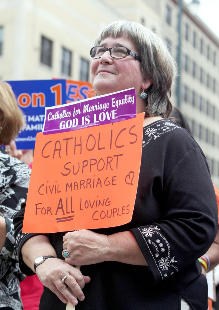 Kathy Tosney holds a sign as she listens to speakers Monday at a rally outside of City Hall in Portland, in support of a ballot question that seeks to legalize same-sex marriage.