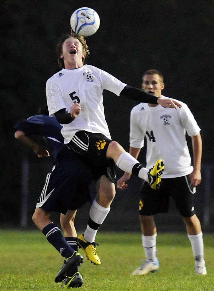 SKY HIGH: Maranacook Community High School's Chris Beckwith heads the ball on the back of Stephen Goodridge, of Oceanside High School, as Maranacook's Zach Elwell, right, looks on during the Black Bears' 3-2 win Tuesday in Readfield.