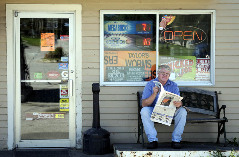 DOWN TIME: Mark Rush catches up on local news Tuesday while taking a break from the register at Randolph Take Out. Rush said the exterior paper break was a good way to experience the mild weather.