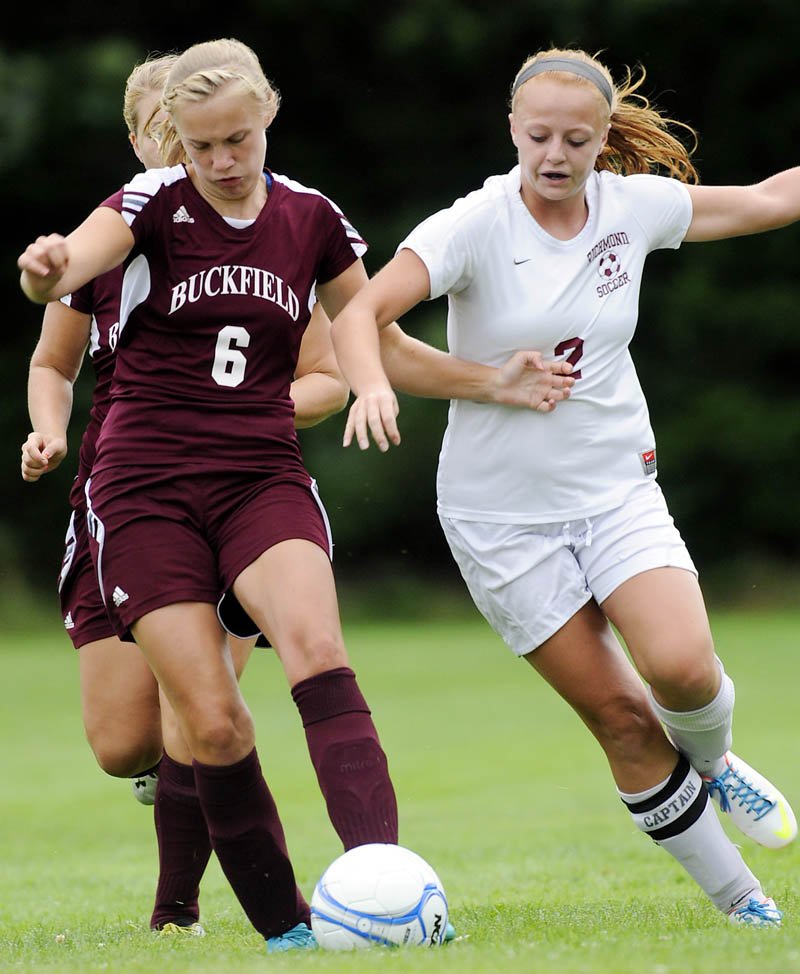 Richmond High School's Noell Acord, right, battles for the ball with Buckfield High School's Elizabeth Strout, left, and Dakota Warren during a soccer game Wednesday in Richmond. The Bobcats won 4-0. For local roundup, see C3.