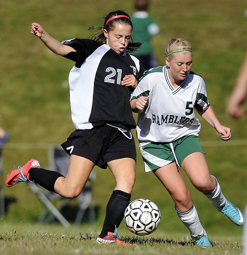 Hall-Dale High School's Signe Lynch, left, tries to get a shot off past Winthrop High School's Annie Guerette during a game Monday in Winthrop. The Bulldogs won 5-1. For local roundup, see C3.