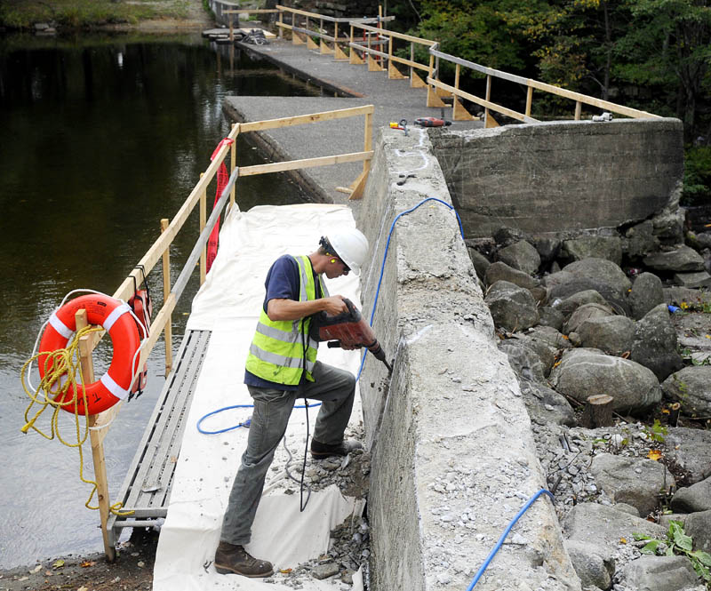 TOUCH UP: Jack Parshall saws a fissure Tuesday into the concrete wall of the North Wayne Dam in Wayne as part of the town's repair of the impoundment. Workers from T Buck Construction, of Auburn, plan to repair cracks in the concrete and replace the stop logs in the dam.