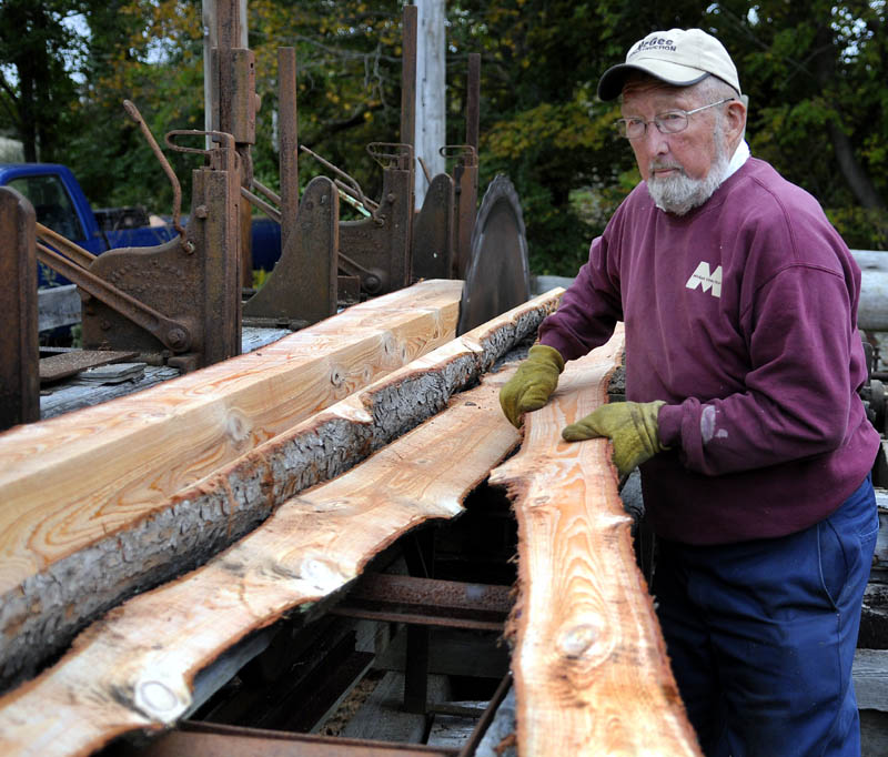 SPLIT: Freeman Lord lugs a slab of hemlock he cut Wednesday at his family's Hallowell saw mill. Lord is cutting beams for a barn he plans to assemble with wood from the family's lot. The mill was built by his father, Roger, the same year Freeman was born, 1940.