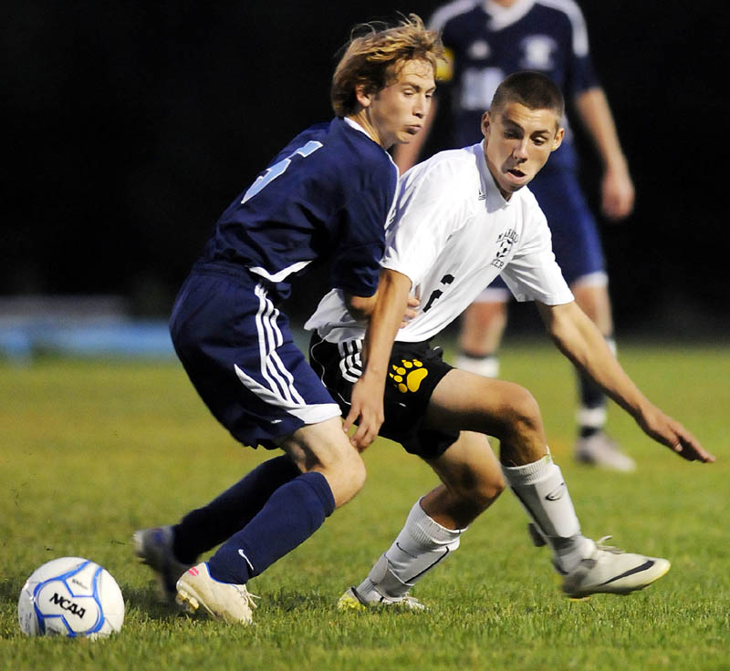 MAKE THE PLAY: Maranacook Community High School's Andrew Poulin, right, battles for the ball with Oceanside High School's Kaleb Robinson during the Black Bears' 3-2 win Tuesday in Readfield.