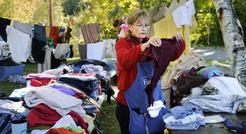 LAWN SALE FUNDRAISER: Barbara Veregge folds clothes Sunday at a lawn sale in Gardiner that raised funds for the treatment of 12-year-old Brandon Ware. The Gardiner child was diagnosed in Boston with a benign tumor on his brain stem.