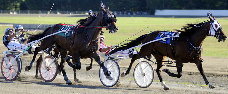 HEAD TO HEAD: Jockey Kevin Switzer Jr, left, on Malek Hanover pulls up on Kevin Switzer, center, on Mr. Nice Guy, as Jason Barlett, on Viper Hanover, tries to pull ahead Sunday during the Windsor Invitational. Kevin Switzer Jr. prevailed with Bartlett finishing second.