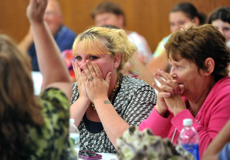 Heidy Mullen, center, reacts after her son's number was picked to fill one of the limited spots in the Cornville Charter School first grade during the lottery at the American Legion hall on Waterville Road, Skowhegan.
