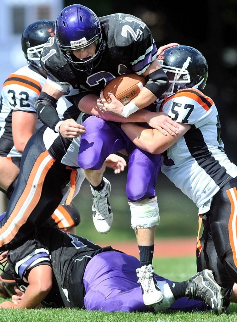 FIGHTING FOR YARDS: Waterville Senior High School running back Racean Wood, center, is tackled by Gardiner's Jory Vermillion, right, in the second quarter of the Tigers' 21-18 win Saturday in Waterville.