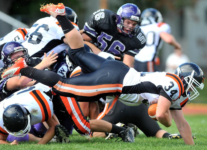 Gardiner running back Seth Wing, 34, dives over a pile of players in the second quarter against Waterville Senior High School in Waterville Saturday.