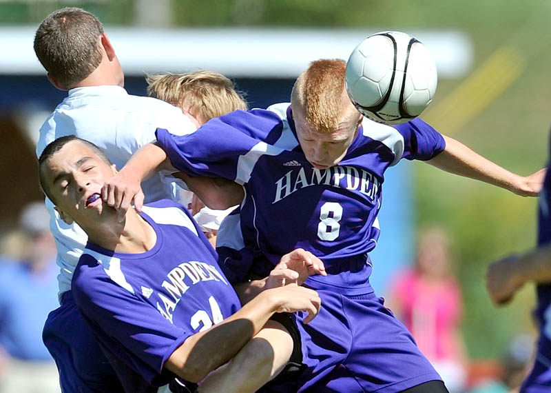 HEADS UP: Hampden Academy teammates Isaac Foster, left, and Eric Babbitt, right, collide as they jump for the header in the first half at against Messalonskee High School on Saturday in Oakland. Hampden beat Messalonskee 6-1.