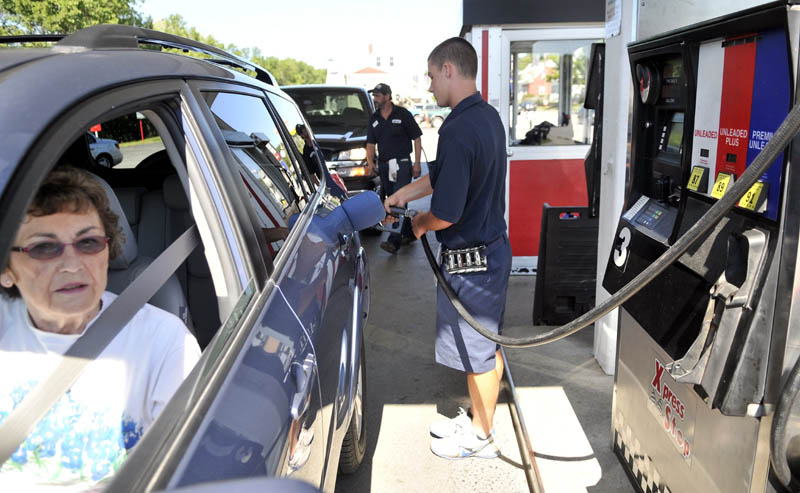 Joseph Hopkins fills the tank for Lorraine Bowdion on Saturday at J&S Oil Xpress Stop on Bay Street in Winslow.