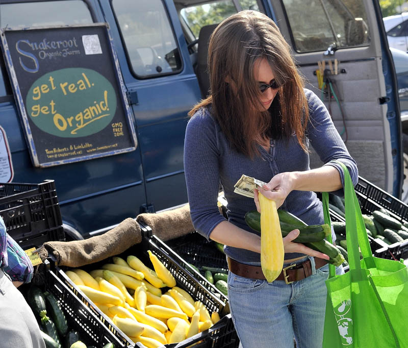 "Kassandra Weese, of Albion, selects some cucumbers and squash from the Snakeroot Organic Farm stand at the Waterville farmers market at The Concourse on Thursday afternoon. A new study released suggests that organic foods have no more nutrients than conventionally grown vegetables. Weese said, ""I buy organic food for two reasons: to avoid pesticides and buy locally."""