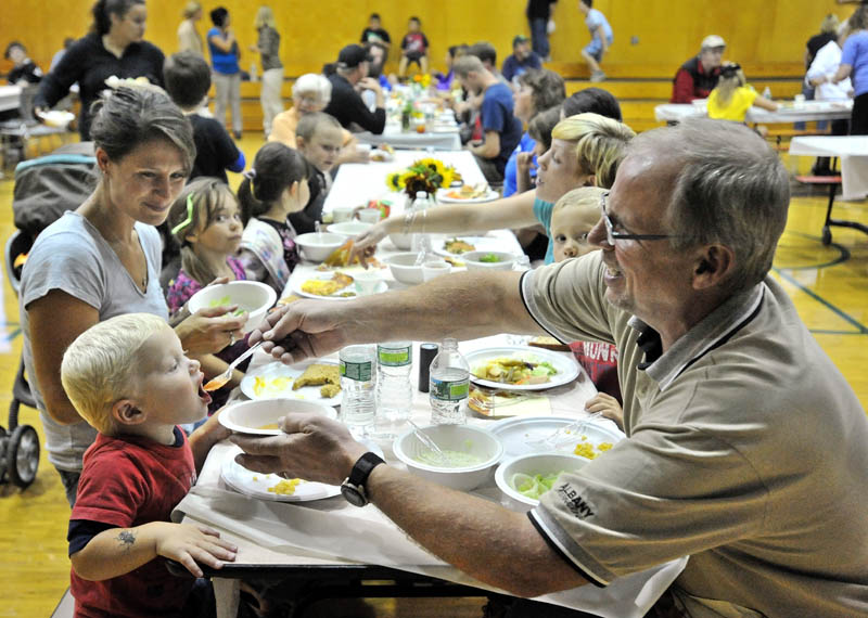 """Dale """"Papa"""" Mullin, right, feeds his grandson Boaz, 2, fresh soup while dining at the harvest dinner at Garrett Schenck Elementary School in Anson Tuesday. Most of the food served was grown in the elementary school garden by students."""