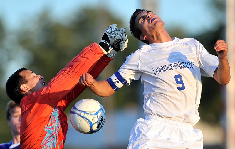 Staff photo by Michael G. Seamans Waterville Senior High School goalie Zachary Disch, left, tries to make a save on a header from Lawrence High School's Drew Bois, 9, right, in the first half of soccer action at Lawrence High School in Fairfield Tuesday night.