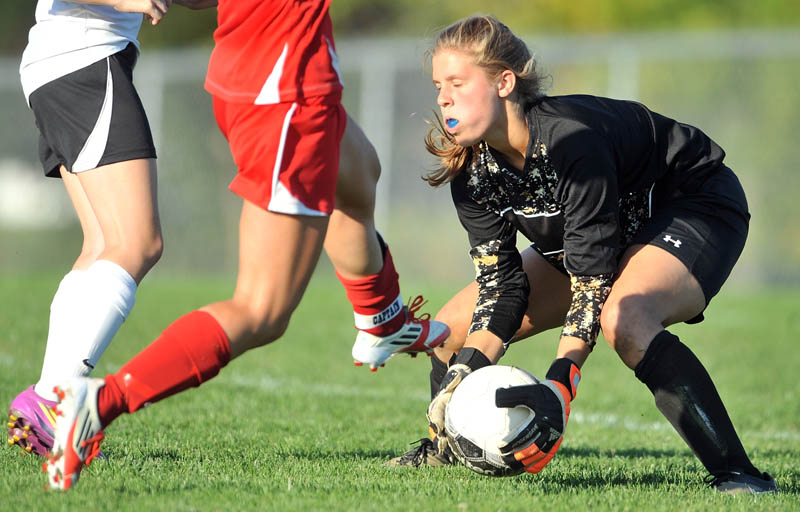 Winslow High School goalie Hillary Libby makes a save as Camden Hills Regional High School's Caroline Matteo tries to score in the second half of the Black Raiders' 4-0 victory Thursday in Winslow.
