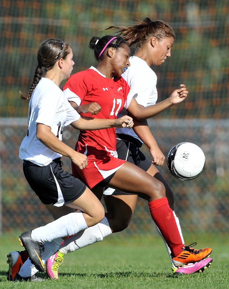 SANDWICHED: Winslow High School's Autumn Poulin, left, and Alliyah Veilleux, right, battle an unidentified Camden Hills player in the second half of the Black Raiders 4-0 win on Thursday in Winslow. Poulin and Veilleux each scored a goal.