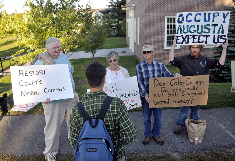 Colby College sophomore Kyle Laurita, foreground, speaks with demonstrators, from left, Bob Shaw, Phyllis Coelho, David Smith and Ed Bonenfant on Wednesday during a protest against the chairman of the college's Board of Trustees Robert E. Diamond Jr. outside the Diamond building at Colby College on Mayflower Hill Road in Waterville.