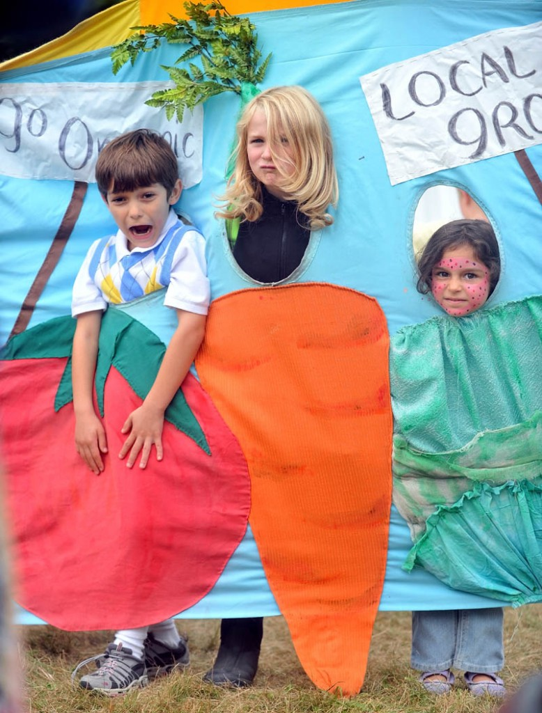 Staff photo by Michael G. Seamans Ashwood Waldorf School students, Jacob Lavi, 7,left, Louis Mainella, 8, center, and Melissa Lavi, 5, right, do their best vegetable impersonation while on a field trip to the Common Ground Fair in Unity Friday.