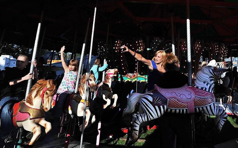 People wave to their friends and family as the Merry-go-Round spins at the Farmington Fair Wednesday afternoon. The fair runs through Saturday Sept. 22.