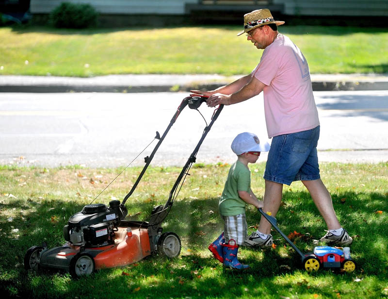 Tom Hubbard gets help mowing the lawn from his grandson Harper, 2, at his son's Mayflower Hill Road residence in Waterville Friday. Hubbard and his wife Ann are in town visitng from Vermont. Hubbard has given his son the old lawn mower and wanted one more drive.
