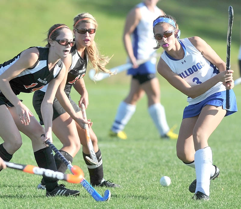 Staff photo by Michael G. Seamans Lawrence High School's Taylor Watson, 3, passes the ball as Brewer High School defenders Lindsay Houp, 14, left, and Rachel Triplett, 12, defend in the first half in Fairfield Tuesday.