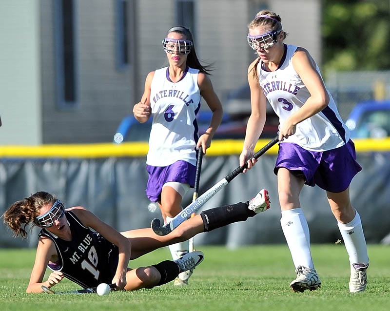 Staff photo by Michael G. Seamans Mt. Blue High School's Taylor Hollingsworth, 18, left, is knocked down as Waterville Senior High School's Kelsea Tortorella, 3, right, and teammate Gabrielle Bridger, 6, center, fight for the ball in the first half at Waterville Thursday.