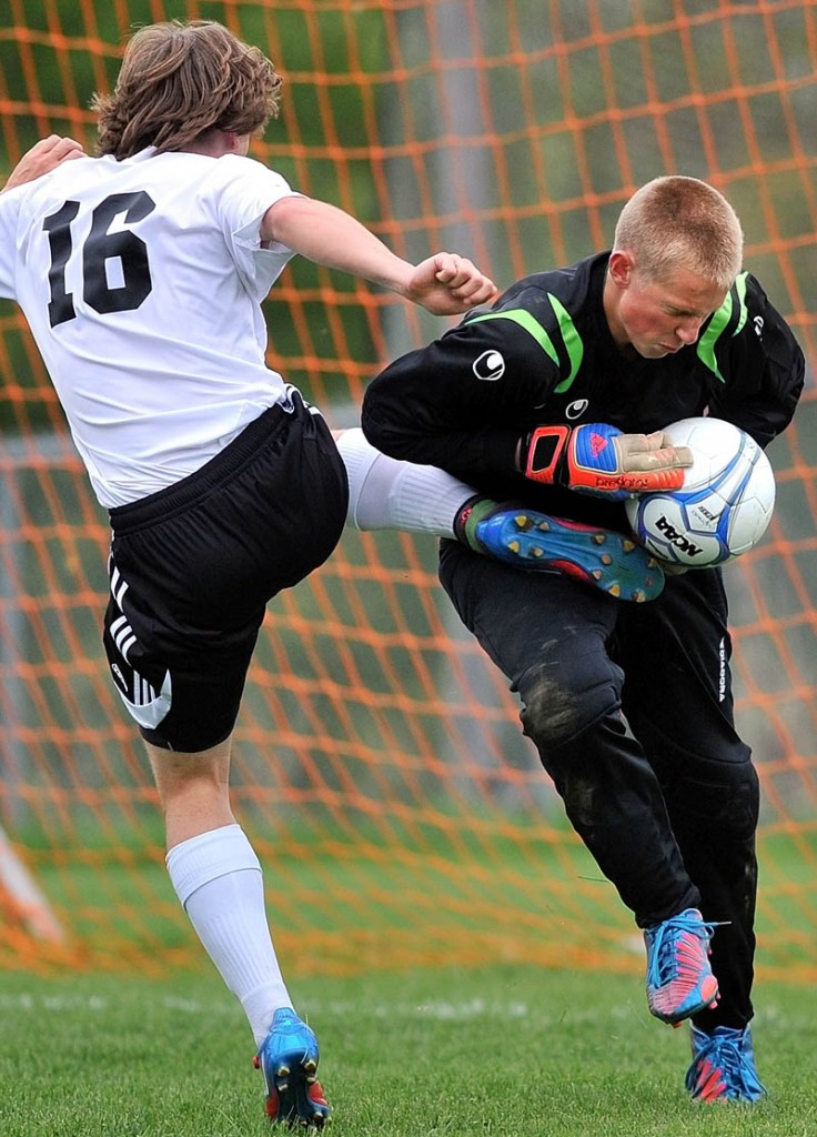 Mt. View High School goalie Mikey Hustus, right, makes a save as Winslow High School's Ryan King, 16, tries to get a foot on the ball in the first half in Winslow Tuesday.