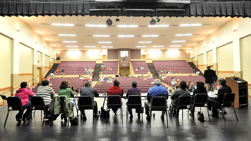 Staff photo by Michael G. Seamans Members of the RSU 18 school board sit on the stage as the RSU 18 district budget meeting is brought to order at Messalonskee High School Thursday.