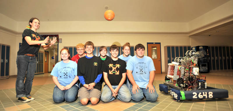 Mike the robot shoots a basketball to Kenzie Brunell, far left standing over members of the Messalonskee High School robotics teammates at Messalonskee High School in Oakland Thursday. Team members kneeling are from left to right Sabine Fontaine, Kenzie Brunelle, Bradley Bickford, Brady Snowden, Amy Pinkham, Robert Klein, Alex Dyer and Justin Shuman.