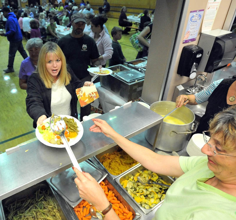 Bonnie Johnson, right, serves fresh vegetables to Sam Richardson at the Harvest dinner at Garrett Schenck Elementary School in Anson. Most of the food served was grown in the elementary school garden by students.