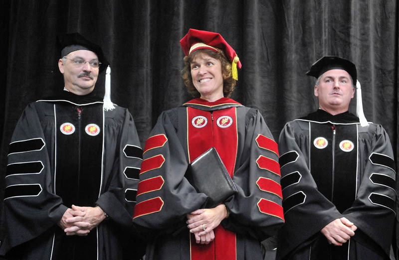 Laurie Gagnon Lachance, center, smiles during her inauguration as fifth president of Thomas College in Waterville, on Saturday. Thomas College board co-chairmen Conrad L. Ayotte, left, and Todd D. Smith, right, stand with the new president.