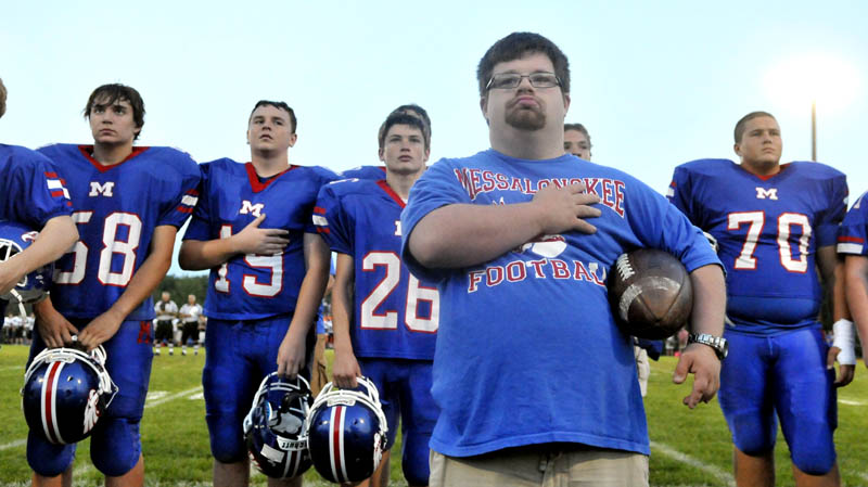 COACH TREVOR: Trevor Perry, front center, stands in front of the Messalonskee High School football team with his hand over his heart during the playing of the national anthem before the Eagles hosted Skowhegan on Friday night in Oakland.